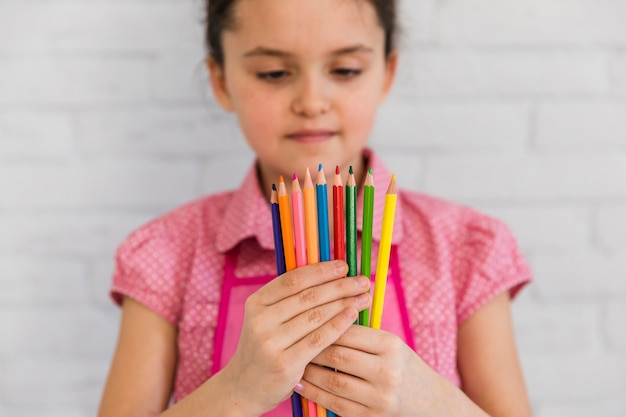 Close-up of a girl looking at multicolored pencils standing against white wall