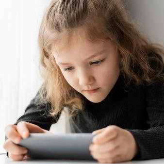 Close-up girl looking at phone