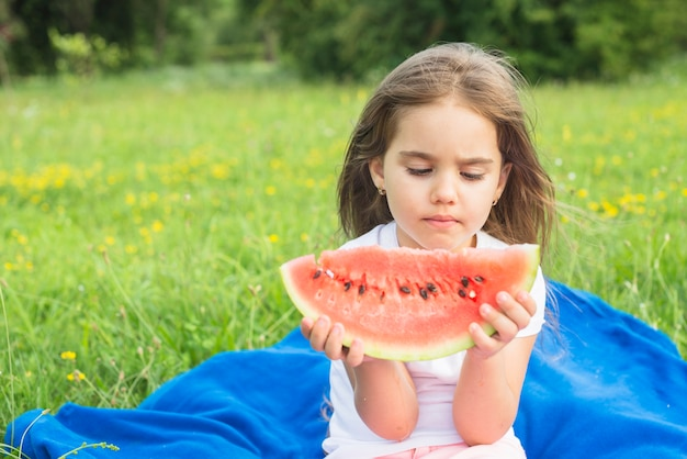 Close-up of a girl looking at watermelon slice in the park