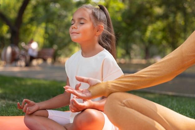 Крупным планом девушка медитирует на открытом воздухе