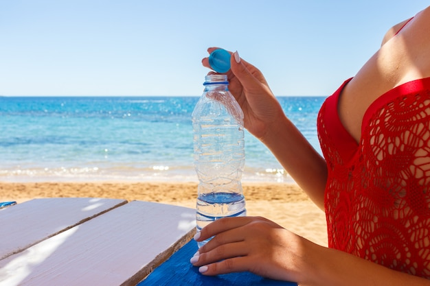 Close-up of a girl opening a plastic water bottle after swimming in the sea