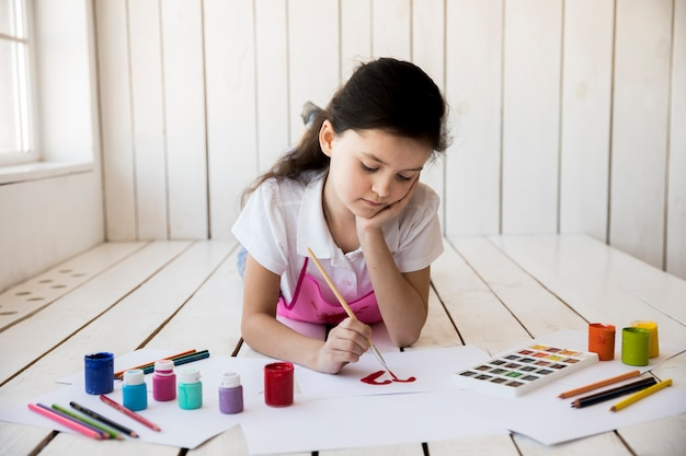 Close-up of a girl painting on the red paper with paintbrush