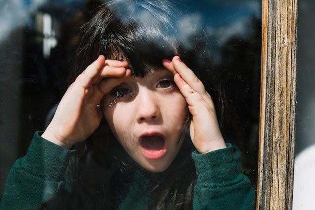 Close-up of a girl peeking through glass window