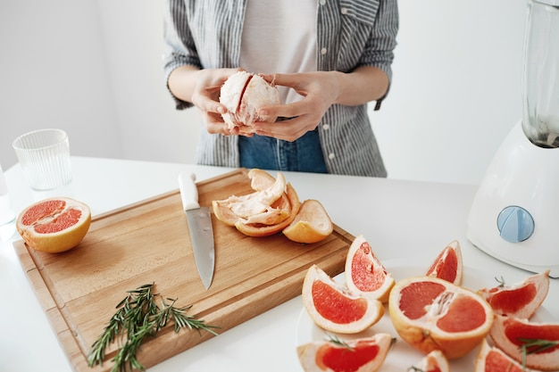 Close up of girl peeling grapefruit over white wall. healthy fitness nutrition concept.