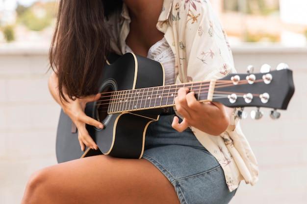 Девушка крупным планом играет на гитаре