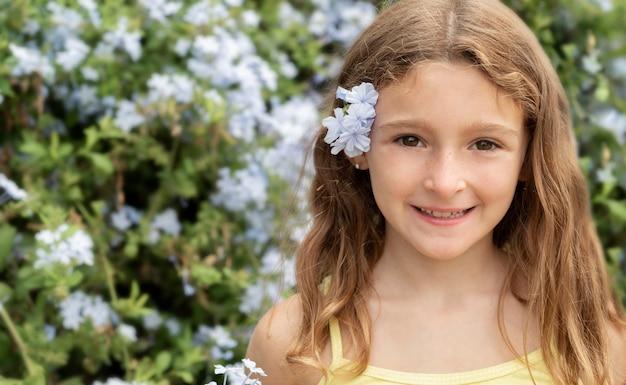 Chiuda sulla ragazza che posa con il fiore nei capelli