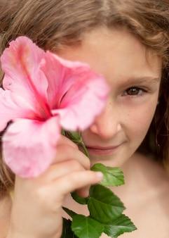 Chiuda sulla ragazza in posa con i fiori