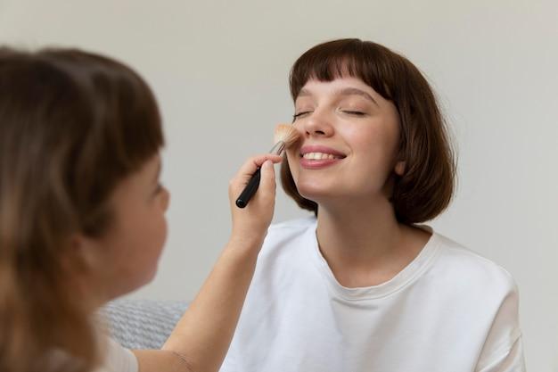 母親に化粧をしている女の子をクローズアップ