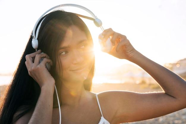 ヘッドフォンを置くクローズアップの女の子