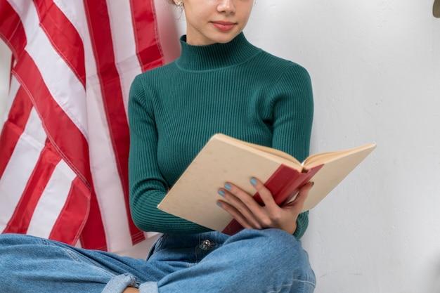 Девушка конца-вверх читая книгу внутри помещения