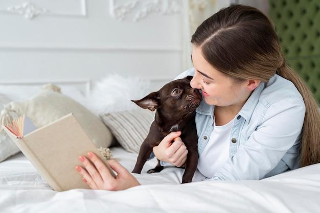 Крупным планом девушка читает в постели с милой собакой