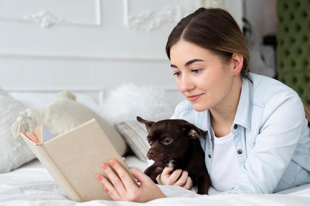 Крупным планом девушка читает в постели с собакой