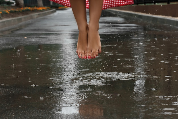 Close up of a girl's feet dancing in a puddle after a summer rain
