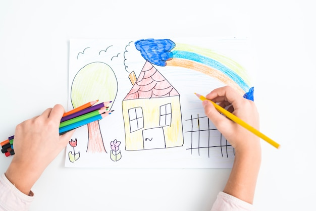 Close-up of girl's hand drawing the house with colored pencil on paper against white backdrop
