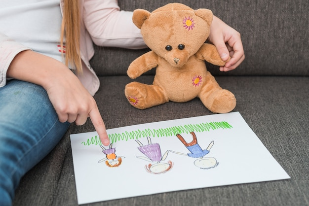 Close-up of a girl's hand showing family drawing made by her to teddy bear on sofa