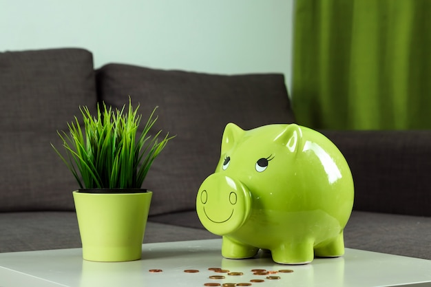 Close-up girl's hand, throws a coin into the piggy bank in the form of a green pig