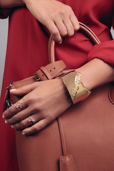 Close up on girl's hands holding brown leather hand bag