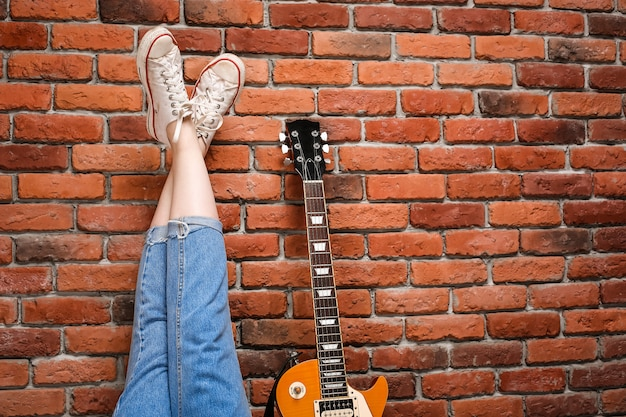 Close up of girl's legs and guitar over brick background.