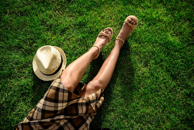 Close up of girl's legs and hat lying on grass.