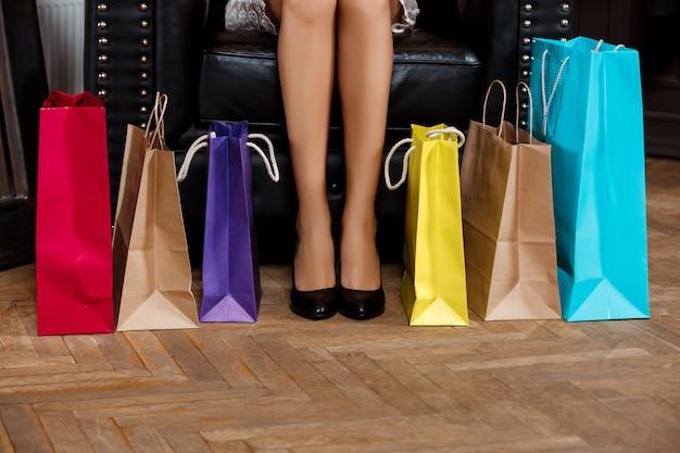 Primo piano delle gambe della ragazza in tacchi e acquisti.