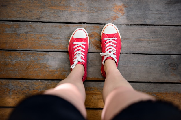Close up of girl's legs in red keds. from above.