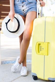 Primo piano delle gambe abbronzate sottili della ragazza. si trova accanto alla valigia gialla con in mano un cappello di paglia e indossa pantaloncini di jeans e scarpe da ginnastica bianche