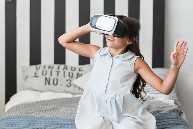 Close-up of a girl sitting on bed wearing virtual reality goggles