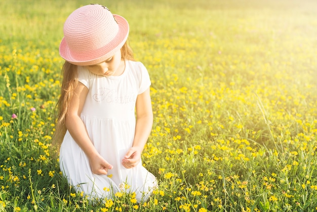 Close-up of a girl sitting in the meadow picking yellow flowers