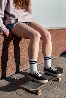 Close up girl sitting on skateboard