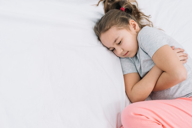 Close-up of a girl sleeping on white bed with pain