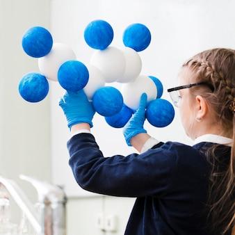 Ragazza del primo piano che studia chimica