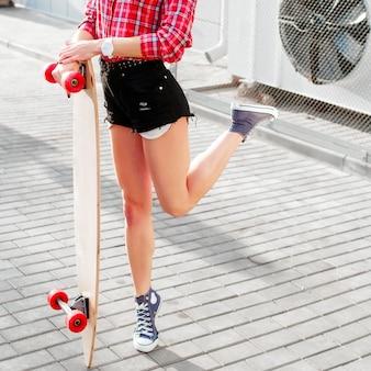 Close-up of girl on tiptoe holding her skateboard