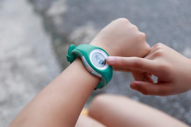 Закройте девушку с помощью сенсорной кнопки smartwatch и сенсорного экрана на активных видах спорта. кнопка касания пальца на смарт-часах. девушка установила умные часы перед тем, как бежать по дороге.