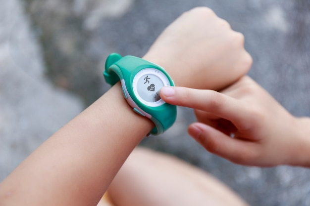 Close up girl using smartwatch touching button and touchscreen on active sports.