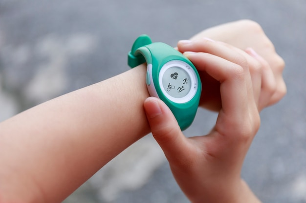 Close up girl using smartwatch touching button and touchscreen on active sports