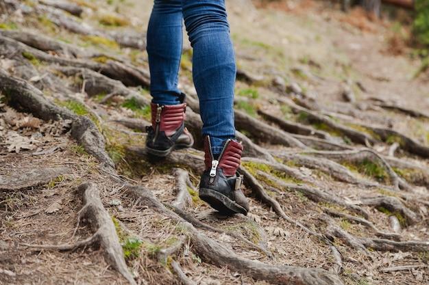 Primo piano della ragazza che cammina su un terreno con le radici