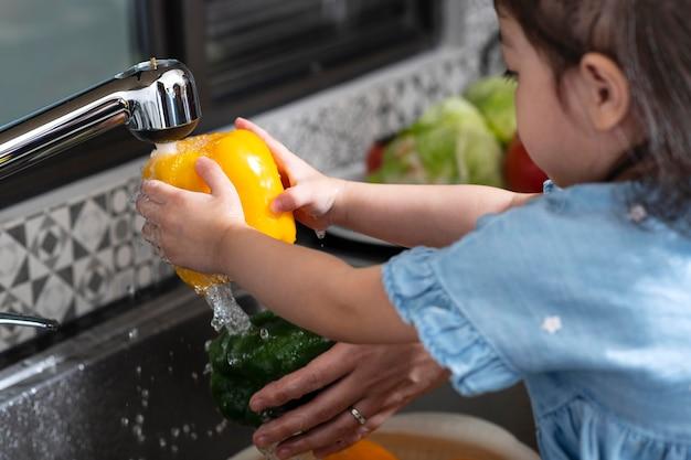 野菜を洗う女の子をクローズアップ
