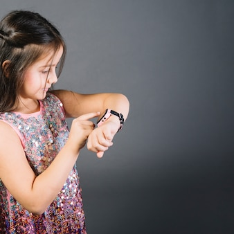 Close-up of a girl watching time on wrist watch against gray background