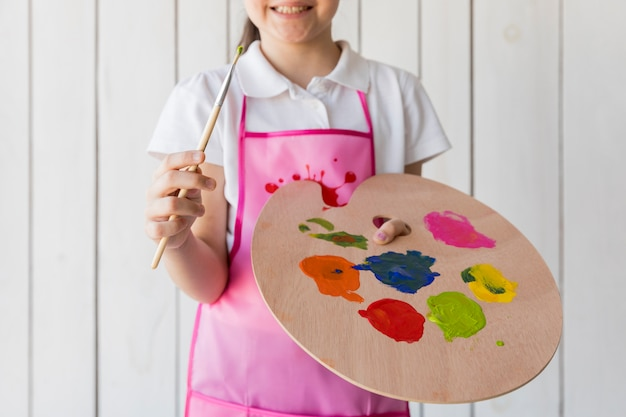 Close-up of a girl wearing paint brush and palette standing against white wooden wall