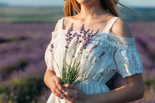 Close-up of a girl in a white dress holding a bouquet of lavender in her hands