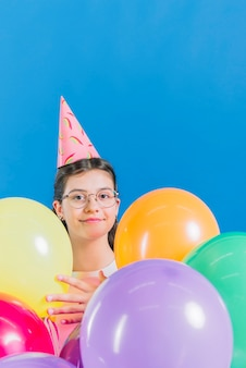 Close-up of a girl with colorful balloons on blue backdrop