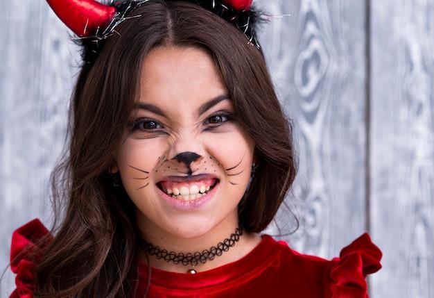 Крупным планом девушка с лицом окрашены на хэллоуин