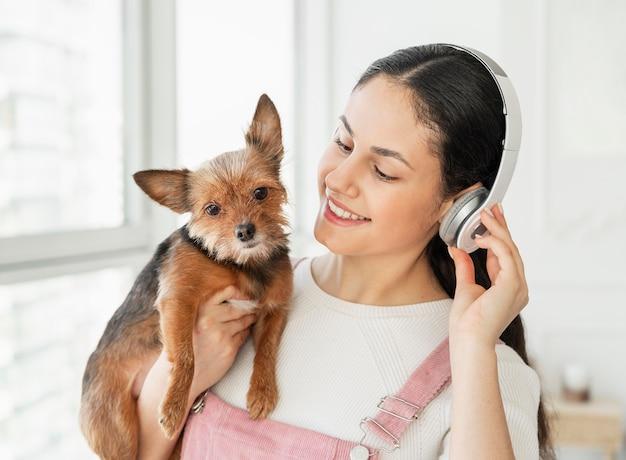 Крупным планом девушка с наушниками и собакой