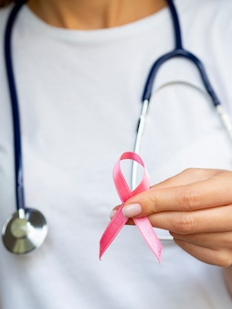 Close-up girl with pink ribbon and stethoscope