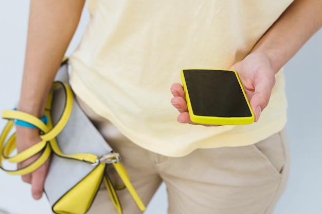Close-up of a girl with a yellow mobile phone and female bag in hands