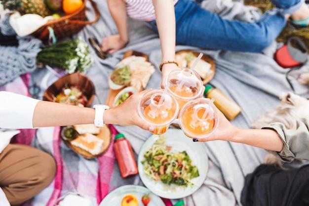 Крупным планом девушки держат чашку с апельсиновым соком на красивом пикнике с разнообразием вкусной еды в парке