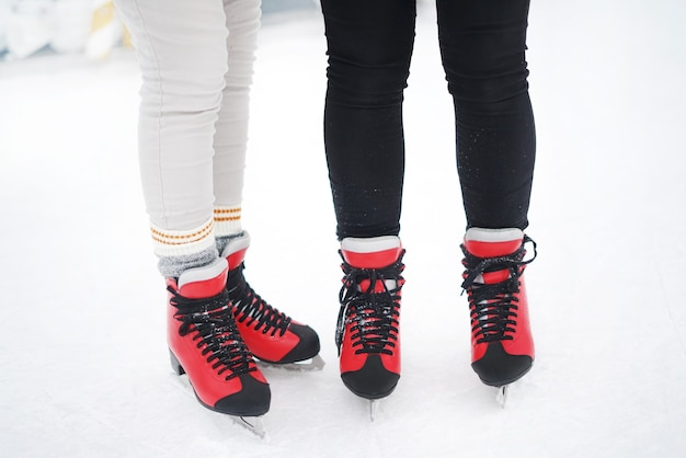Close-up of girls standing in red skates on the ice arena