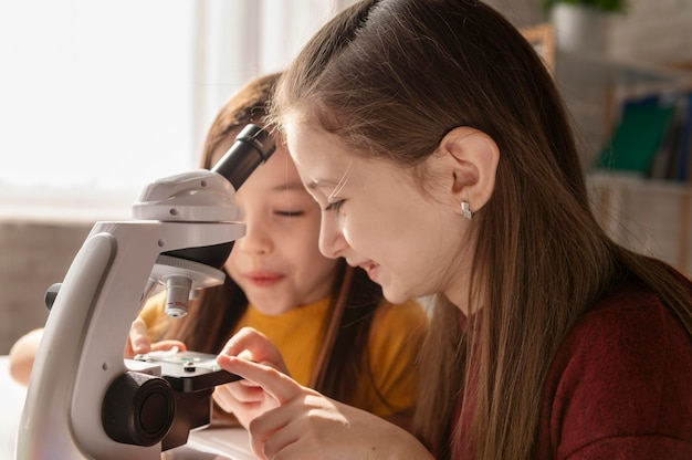 Close up girls with microscope
