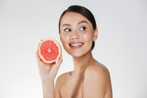 Close up of glad woman with healthy fresh skin holding juicy grapefruit and looking aside with smile, isolated over white