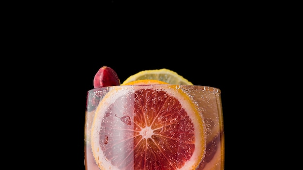 Close-up glass of acidified beverage with orange